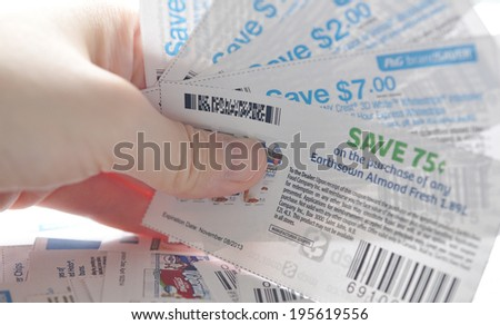 Coquitlam, BC, Canada - May 25, 2014 : Close up holding saving coupons. All coupons for Canadian store, they are issued by manufacturers of consumer packaged goods or by retailers in Canada. - stock photo