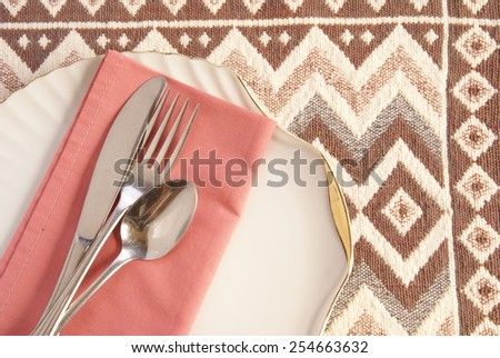 Coral pink table napkin on a gold rimmed white plate with polished metal silverware on top. Table cloth or placemat lends a southwestern touch. - stock photo