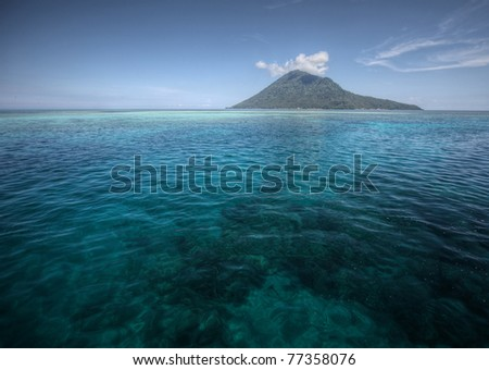 Coral reef transparent sea and white clouds. Bunaken island. indonesia - stock photo
