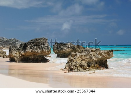 Coral rocks on a beautiful secluded pink sand Bermuda beach. - stock photo