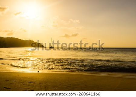 Coral sandy beach in the sunset light. In the distance a sailing yacht. Seychelles. - stock photo