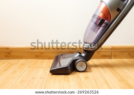 Cordless vertical vacuum cleaner cleaning parquet floor. - stock photo