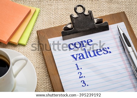 core values list on clipboard  with a pen, coffee and sticky notes against burlap canvas - business ethics and mission concept - stock photo
