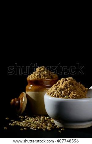 Coriander Powder and seeds on black background. - stock photo
