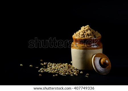 Coriander Powder in clay pot with seeds on black background.  - stock photo