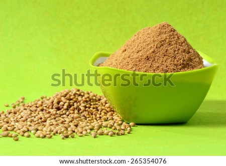 Coriander seeds and Powdered coriander in green container on green background - stock photo