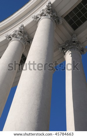 Corinthian columns against vivid blue sky, view from below