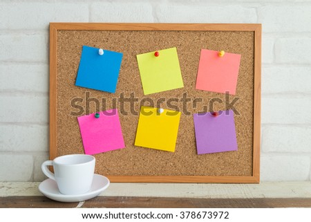 Cork board with colorful blank notes and white coffee cup - stock photo