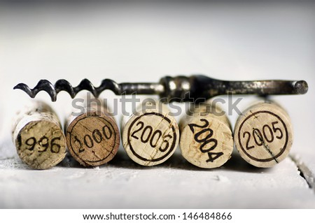 Corks of different wine years and corkscrew - stock photo