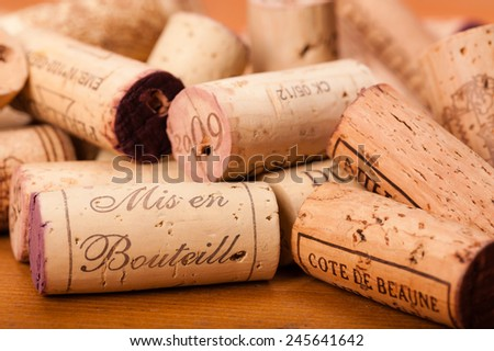 "Corks on wood. "" Mis en Bouteille"" (which means ""filled in the bottle or bottled""), the Origin of the Wine and or the Vintage is printed on them. Cote de Beaunes Villages is a french Region for Wine. - stock photo"