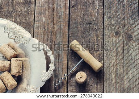 corkscrew and cork from wine on the old dark wooden background in metal plate toning - stock photo