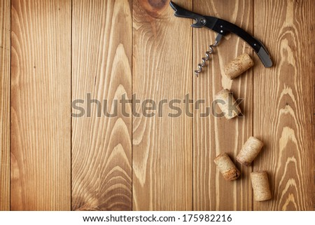 Corkscrew and wine corks on wooden table background with copy space - stock photo