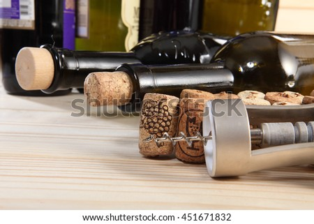 Corkscrew, corks and bottle of wine. Selective focus