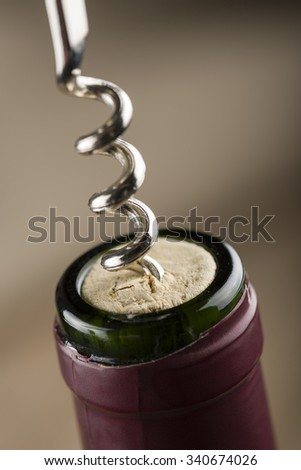 corkscrew inserted on cork into red wine bottle, closeup. - stock photo