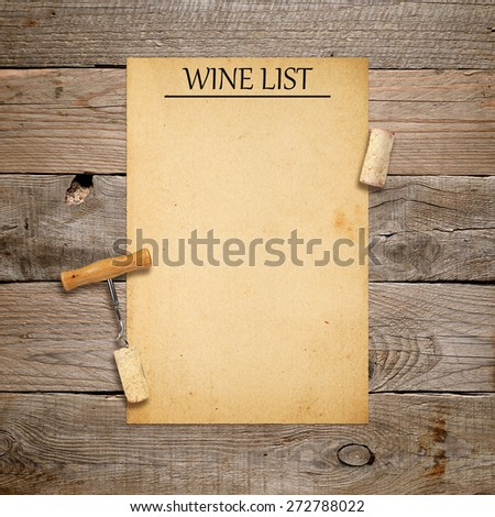 Corkscrew with cork and blank wine list on old wooden background - stock photo
