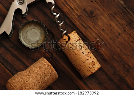Corkscrew with corks and bottle cap on rustic wood background.  Low key still life with directional natural lighting for effect.  - stock photo