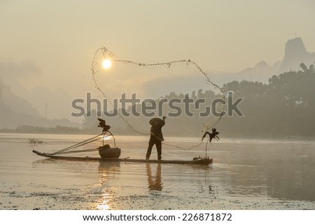 Cormorant fisherman throws a net with ancient bamboo boats at sunrise - Xingping, China - stock photo