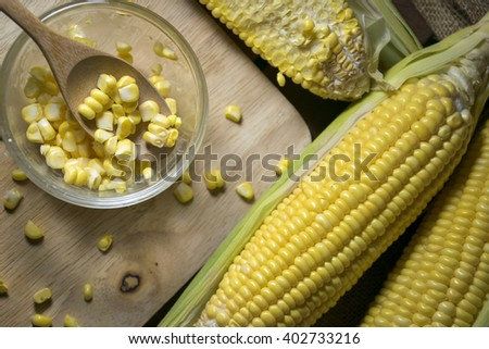 Corn and corn slide in a cup with wooden spoon - stock photo