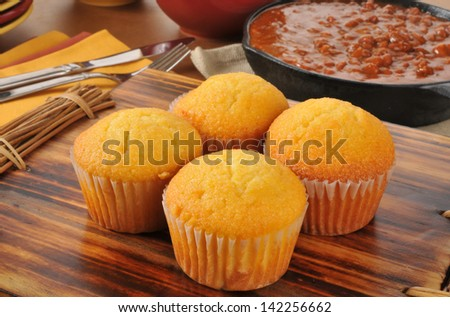 Corn bread muffins with a cast iron skillet of chili con carne in the background - stock photo