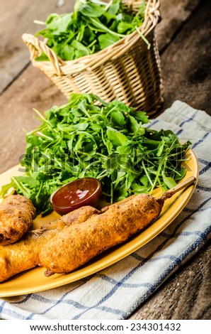 Corn dog with fresh arugula salad and hot dip, wood table - stock photo