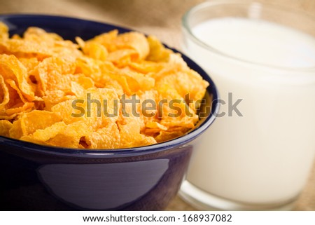 Corn Flaked Breakfast Cereal - This is a shot of a bowl of corn flake cereal and a glass of milk shot with a shallow depth of field with a burlap background. - stock photo