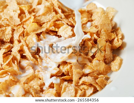 Corn flakes breakfast with milk being poured over it - stock photo