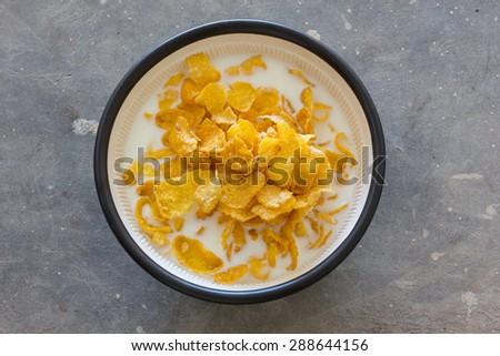 Corn flakes heap in a glass bowl on concrete - stock photo