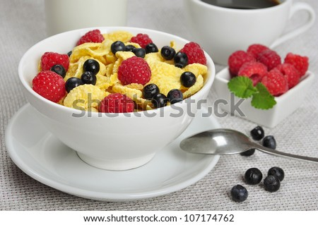 Corn flakes, raspberry and  blueberry in white bowl close up