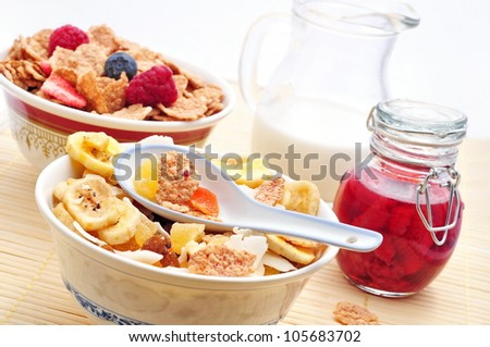 Corn flakes with fresh fruits, milk and jam - stock photo