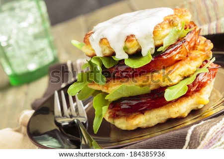 Corn fritters stacked with roasted tomatoes and arugula, served with ranch dressing - stock photo