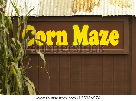 Corn Maze painted in yellow along the side of a brown shed - stock photo