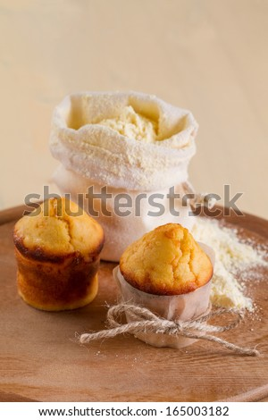Corn muffins and a bag of flour on the round board