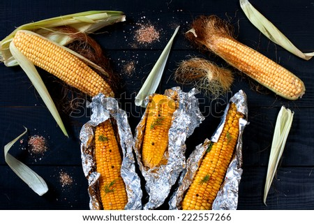 Corn on the cobs, baked in foil on the black wooden table, top view - stock photo
