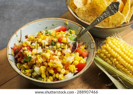 Corn salsa with tomatoes and onions in a bowl, selective focus - stock photo