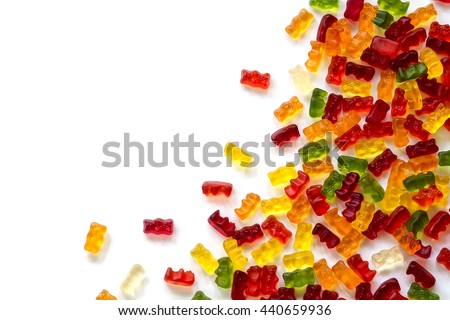 corner background made of colorful fruit gum candies isolated with small shadow on white, generous copy space - stock photo