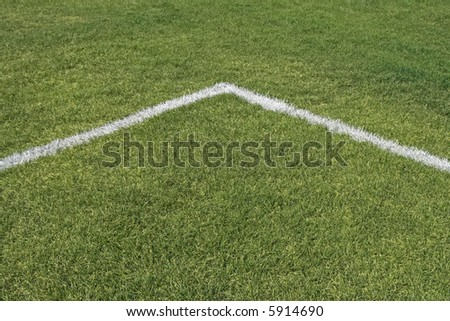 Corner boundary lines of a green grass playing field. - stock photo