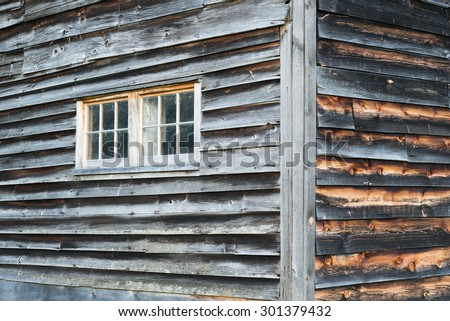 Corner Detail of Weathered Barn Walls with Two Windows and Rustic Gray and Brown Wood Siding.  - stock photo