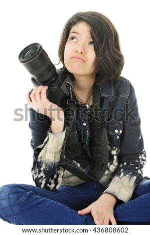Corner image of a young teen photographer looking up wonderingly as she supports her pro camera on her shoulder.  On a white background. - stock photo