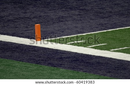 Corner of a football field blue end zone with orange pylon - stock photo