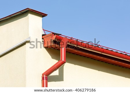 corner of a house with rain gutter and metal roof - stock photo