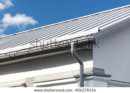 corner of house with gray metal roof and drainpipe - stock photo