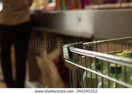 corner of shopping trolley in supermarket checkout queue. - stock photo