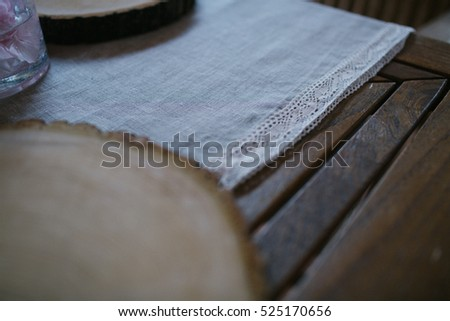 Corner of white tablecloth decorated with laces