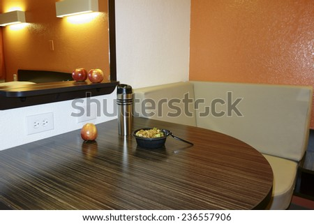 Corner table with lunch bowl, thermos and fruits - stock photo