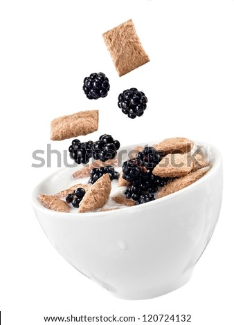 Cornflakes and blackberries  flow in a cup with milk - stock photo