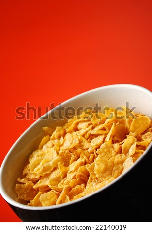cornflakes in bowl isolated over red background (shallow DOF)