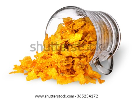 Cornflakes spill out of a glass cup isolated on white background - stock photo