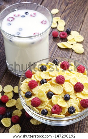 Cornflakes with berries and cup of milk on wooden table - stock photo