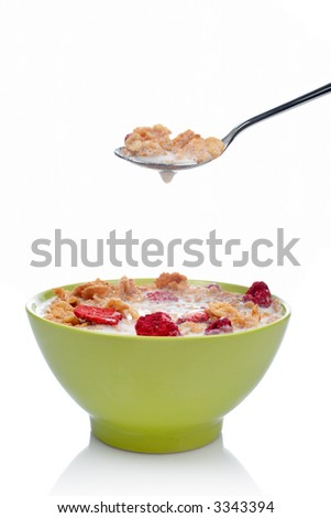 Cornflakes with fruits on the spoon above the green bowl. Shallow DOF
