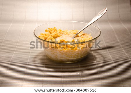 Cornflakes with milk in the white bowl.